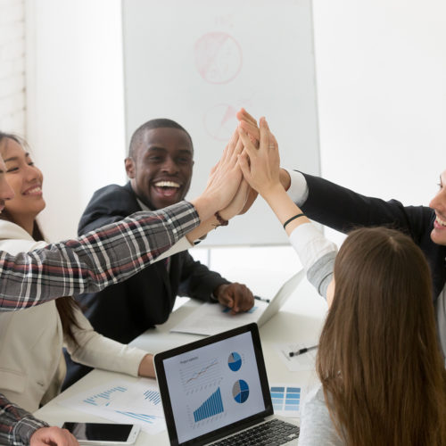 Excited diverse millennial group giving high five celebrating online business win or shared goal achievement, colleagues congratulating with good result, performing team building. Rewarding concept